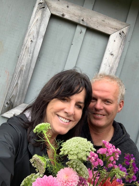 a man and woman smiling and holding flowers