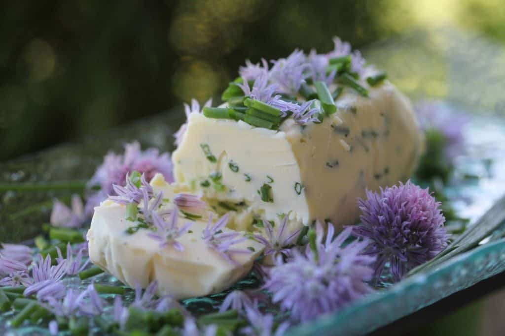 chive butter on a glass plate, garnished with bits of chive and chive blossoms, showing how to use fresh chives from the garden