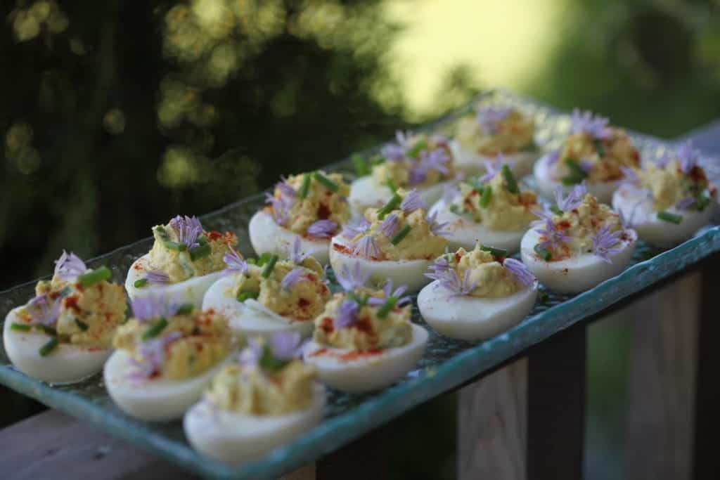 deviled eggs on a glass plate, showing how to use fresh chives from the garden