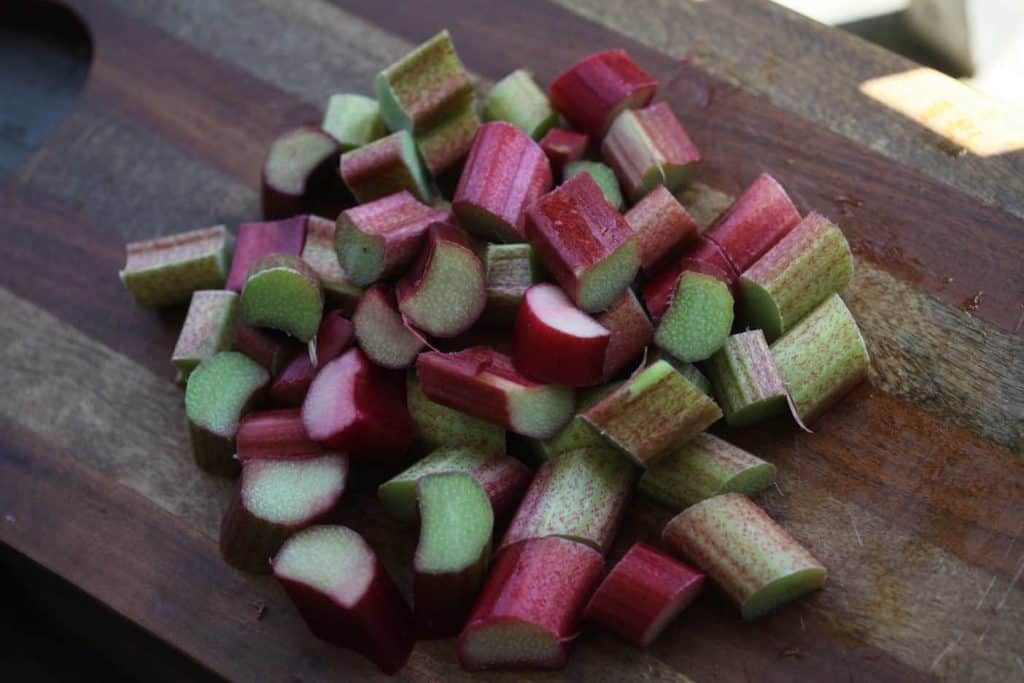 chopped rhubarb pieces on a wooden cutting board