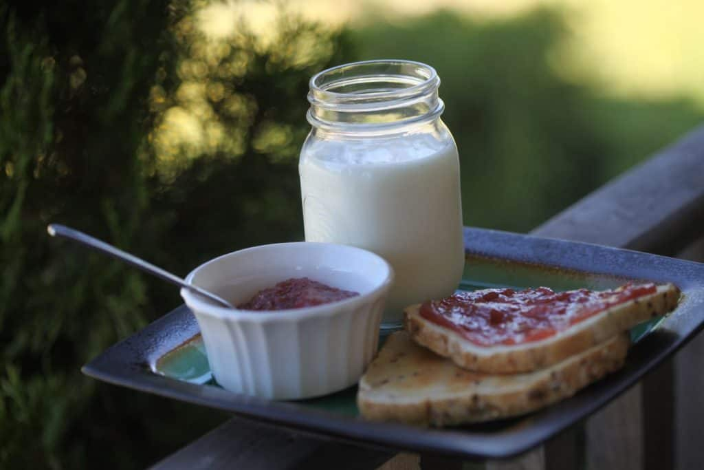 a square plate holding a mason jar of milk, a white bowl filled with jam and a spoon, and two pieces of toast with jam