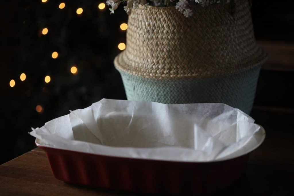 a baking dish with parchment paper in front of a basket with fairy lights in the background