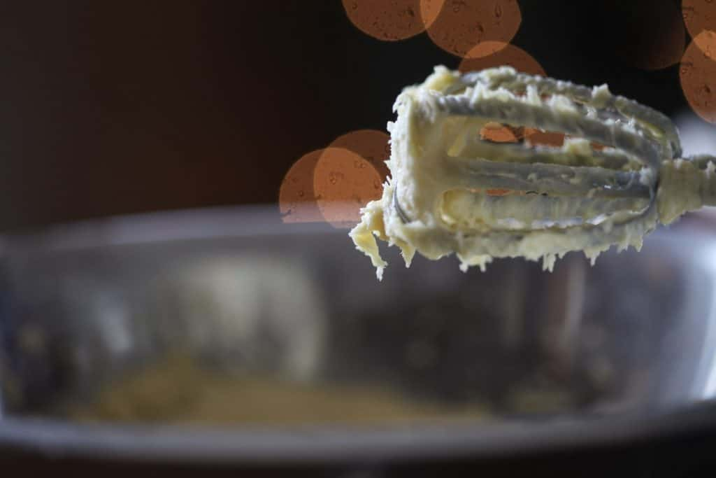 a beater covered  with batter next to a silver bowl, with bokeh lights in the background