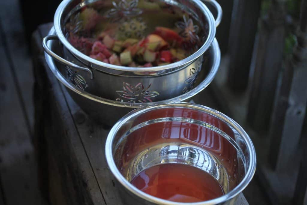 a colander containing chopped rhubarb and a silver bowl containing pink rhubarb juice on a grey wooden box