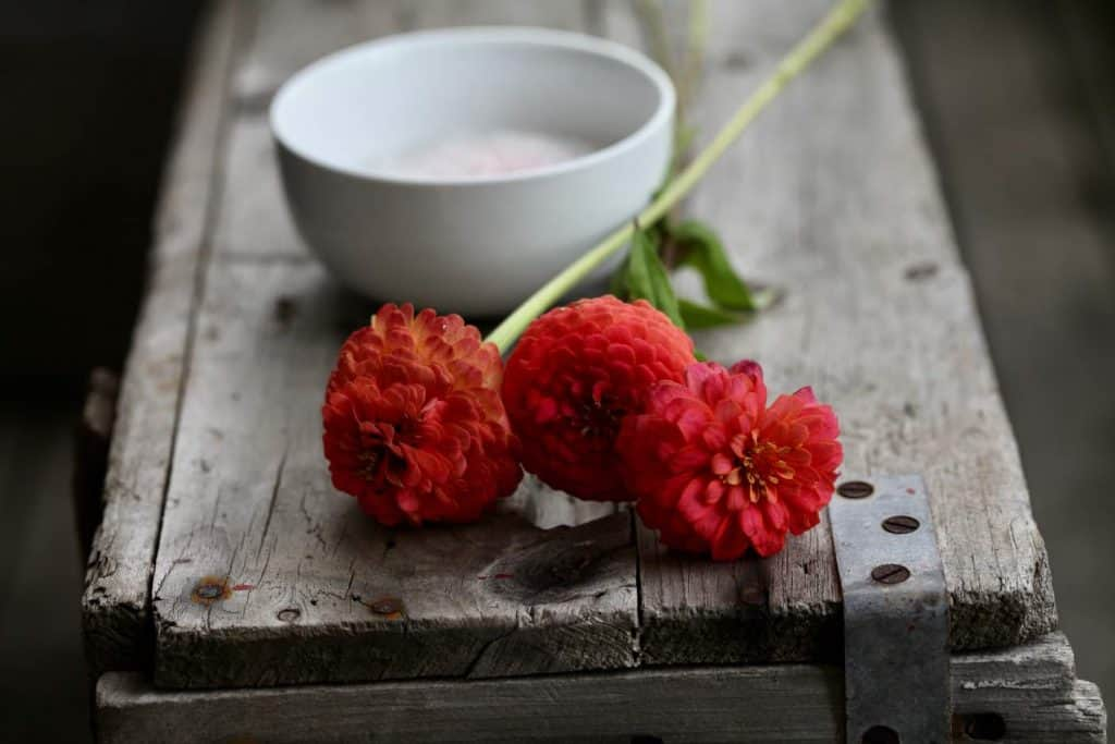 red flowers and silica gel on a wooden crate