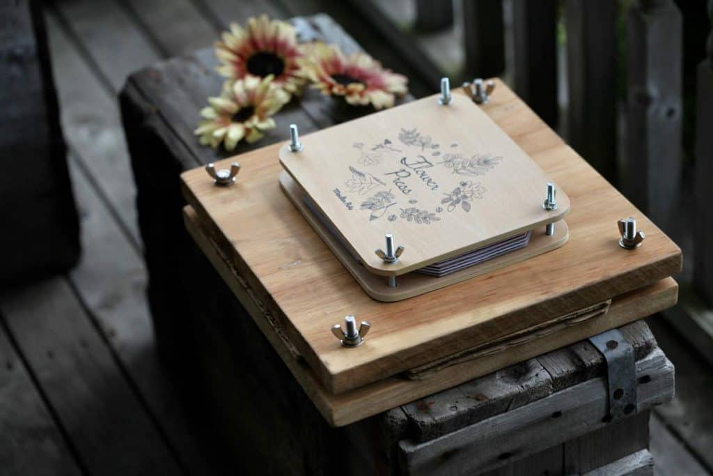 two flower presses of different size, on a grey wooden crate with sunflowers in the background