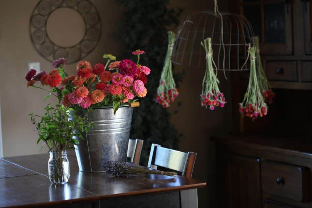 a room containing multiple containers containing flowers and foliage, and a metal basket inverted with hanging globe amaranth