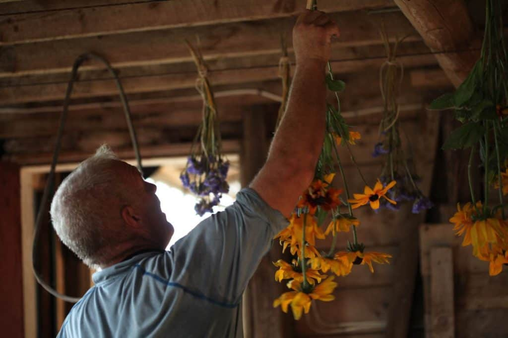a man hanging flowers to dry