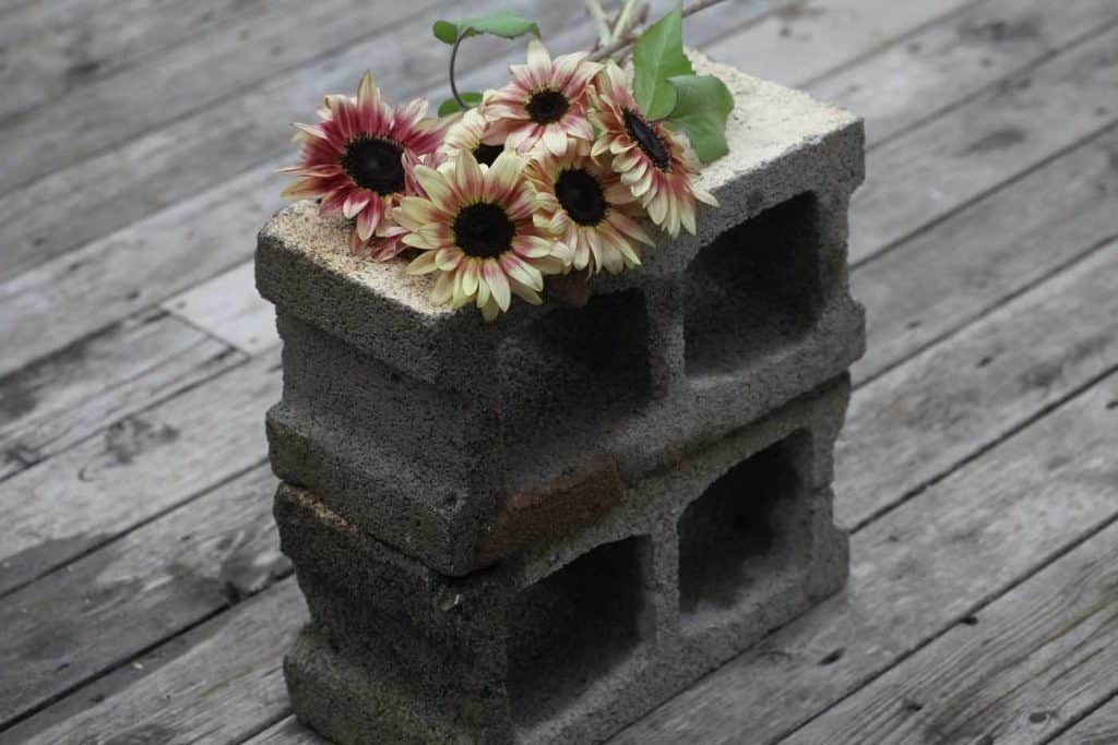 two cement bricks topped with sunflowers