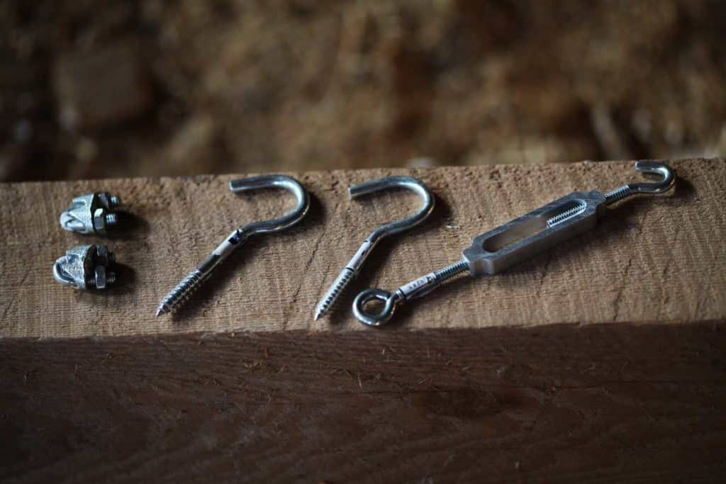supplies for drying line- cable clamps, screw hooks, and turnbuckle laying on a wooden beam