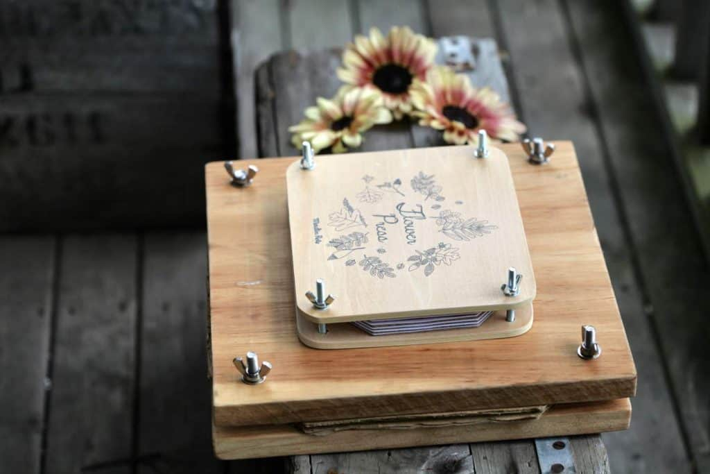 two flower presses next to sunflowers on a grey wooden crate